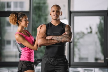 Photo pour Musculaire afro-américain athlète masculin posant avec les bras croisés tandis que sa copine debout près au gymnase - image libre de droit