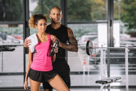 young african american sportsman embracing girlfriend with sport bottle and towel at gym