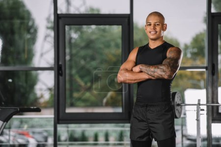 portrait of african american sportsman posing with crossed arms at gym