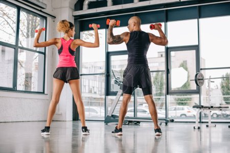 rear view of african american couple of athletes exercising with dumbbells at gym