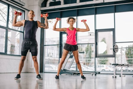 smiling young african american couple of athletes exercising with dumbbells at gym