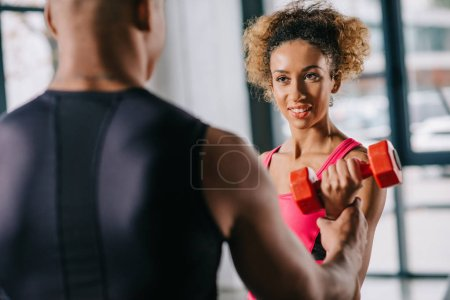 Photo for Partial view of african american male trainer helping sportswoman to exercising with dumbbell at gym - Royalty Free Image