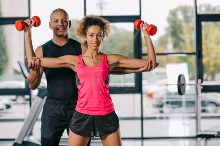 Photo for Young african american male trainer helping sportswoman to exercising with dumbbells at gym - Royalty Free Image