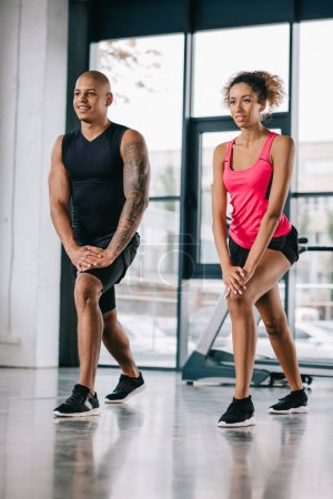 smiling african american couple of athletes doing exercise at gym