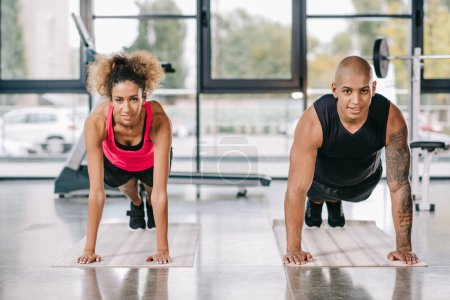 happy young african american couple of athletes doing plank on fitness mats at gym