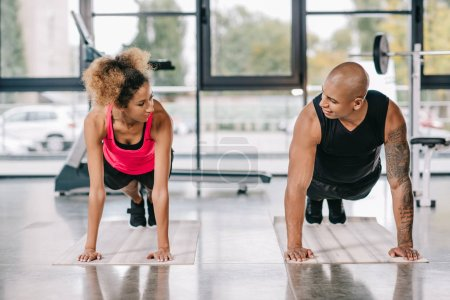 smiling african american couple of athletes looking at each other and doing plank on fitness mats at gym