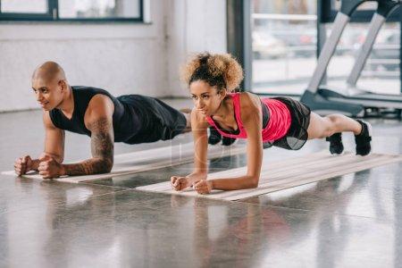 Photo pour Jeune couple afro-américain d'athlètes faisant planche sur tapis de fitness à la salle de gym - image libre de droit