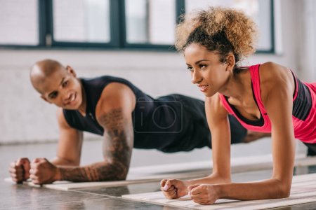 attractive african american sportswoman doing plank with her boyfriend at gym