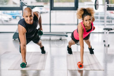 cheerful african american couple of athletes exercising with dumbbells on fitness mats at gym