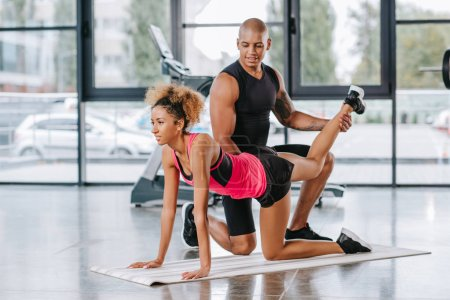 muscular african american male trainer helping sportswoman to stretching at gym