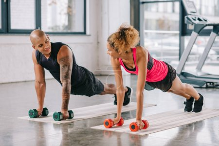 couple of athletes looking at each other and exercising with dumbbells on fitness mats at gym
