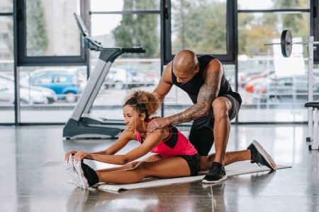 tattooed african american male trainer helping sportswoman to stretching at gym