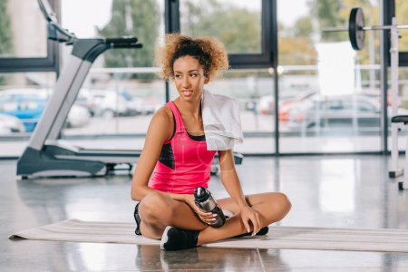 Photo for Attractive african american female athlete with towel and sport bottle resting on fitness mat at gym - Royalty Free Image