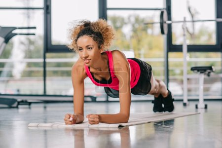 happy african american sportswoman doing plank on fitness mat at gym