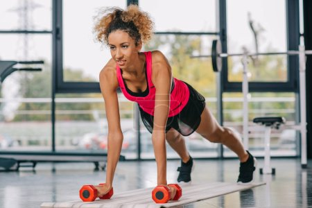 Photo for Young african american sportswoman doing plank with dumbbells on fitness mat at gym - Royalty Free Image