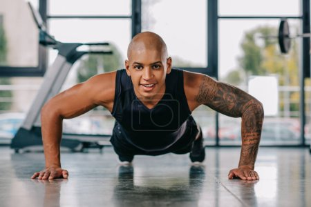 selective focus of tattooed young sportsman doing push ups at gym