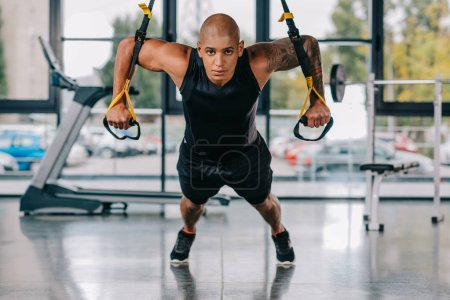 african american sportsman looking at camera and exercising on fitness straps at gym