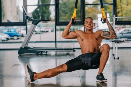 cheerful african american sportsman exercising on suspension straps at gym