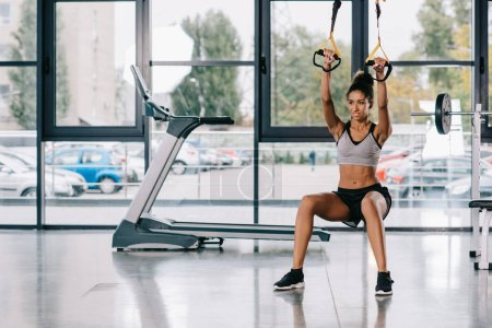 selective focus of  african american sportswoman exercising on fitness straps at gym