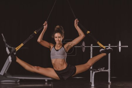 smiling african american sportswoman stretching on suspension straps at gym