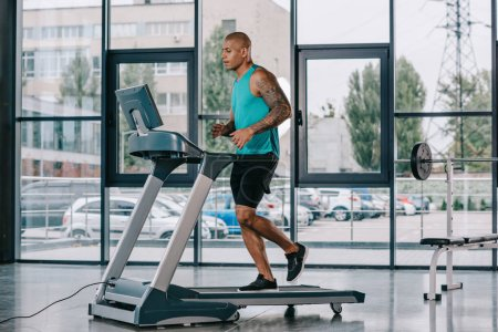 Photo for Side view of young african american sportsman running on treadmill at gym - Royalty Free Image