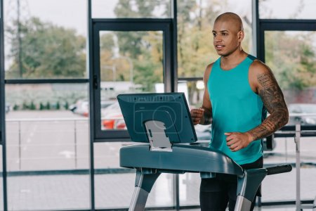 young african american sportsman running on treadmill at gym