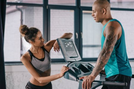 young female trainer looking at african american sportsman running on treadmill at gym