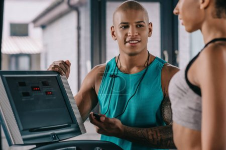 selective focus of african american male trainer with timer looking at sportswoman running on treadmill at gym