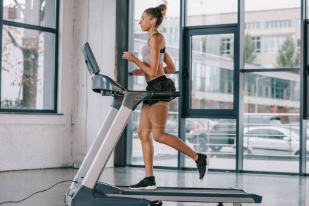 Photo for Side view of african american sportswoman running on treadmill at gym - Royalty Free Image