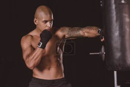 tattooed african american male boxer in boxing bandage training with punching bag at gym