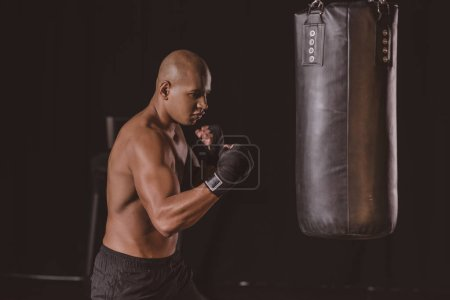 young african american male boxer in boxing bandage training with punching bag at gym
