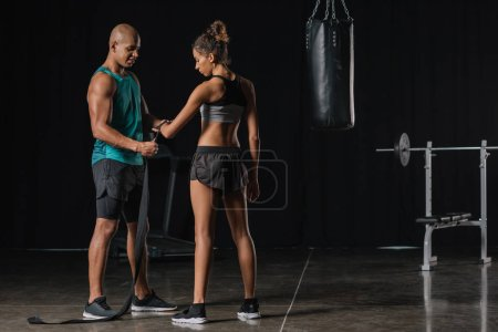 muscular african american male trainer wrapping female boxer hand in boxing bandage at gym