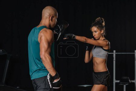 rear view of african american male trainer exercising with female boxer at gym
