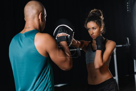 Photo for Rear view of muscular male trainer exercising with female boxer at gym - Royalty Free Image