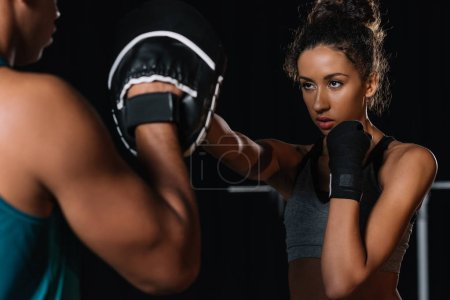 partial view of male personal trainer exercising with female boxer at gym