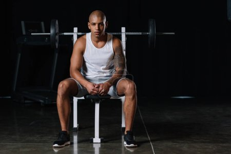serious african american male athlete looking at camera and sitting at gym
