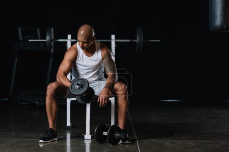 african american young sportsman exercising with dumbbell at gym