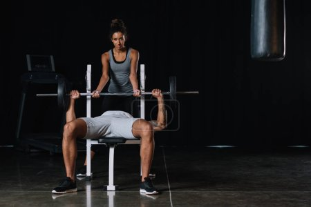 young african american woman helping boyfriend to exercising with barbell at gym