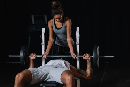 african american woman helping boyfriend to exercising with barbell at gym