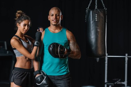 selective focus of african american couple of boxers standing near punching bag at gym