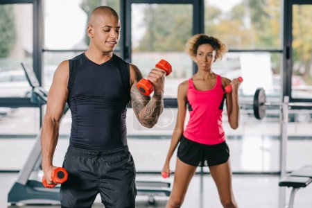 souriant afro-américain entraîneur masculin formation jeune femme à l'exercice avec haltères à la salle de gym