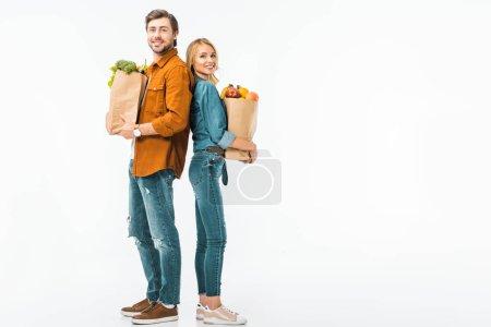 Photo pour Couple heureux avec des sacs pleins de produits debout dos à dos isolés sur blanc - image libre de droit