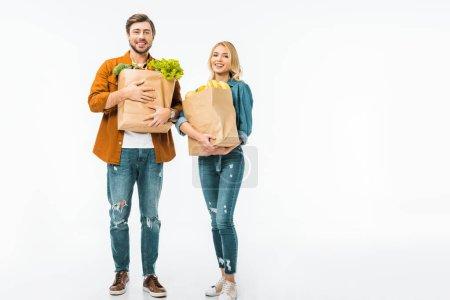 Photo pour Couple jeune positive avec des sacs en papier remplis de produits isolés sur blanc - image libre de droit
