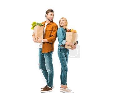 Photo pour Couple avec des sacs pleins de produits regardent et debout dos à dos isolé sur blanc - image libre de droit