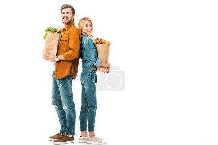 Photo pour Couple gai avec des sacs pleins de produits debout dos à dos isolés sur blanc - image libre de droit