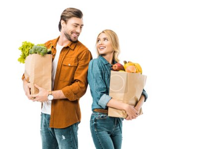 Photo pour Sourire de couple avec des sacs pleins de produits regardent et debout dos à dos isolés sur blanc - image libre de droit