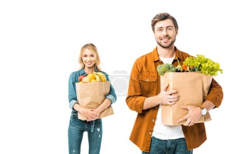 Photo pour Bel homme souriant tenant le panier avec les produits tandis que sa copine debout derrière isolé sur blanc - image libre de droit