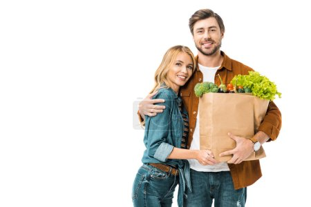 young man holding paper bags with products and embracing girlfriend isolated on white
