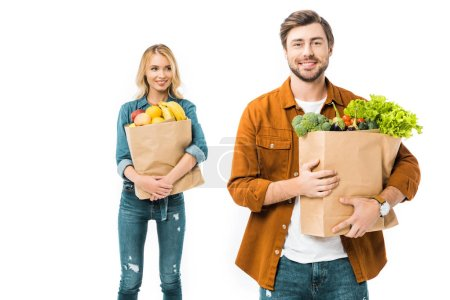 happy young man holding shopping bag with products while his girlfriend standing behind isolated on white