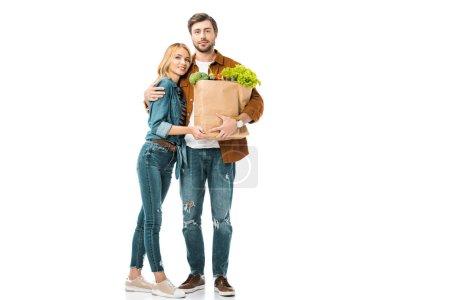 Photo pour Gai homme tenant des sacs en papier avec produits et embrassant la copine isolée sur blanc - image libre de droit